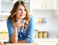 Woman in kitchen drinking a glass of water