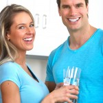 Man and woman in kitchen making a toast with glasses of water